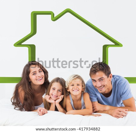 Happy family lying on a bed against house outline - stock photo