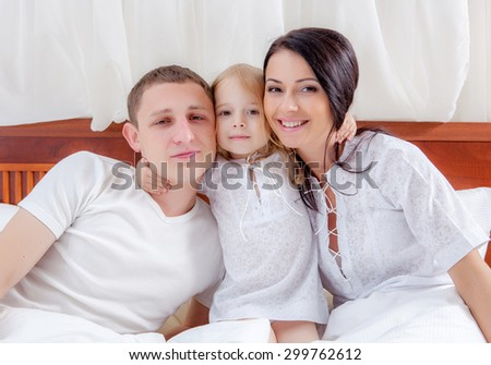 Happy family lying on a bed together in the bedroom - stock photo