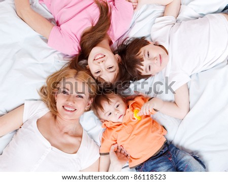 Happy family lying on bed and looking into camera - stock photo