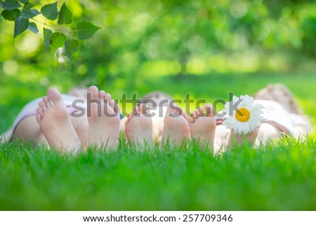 Happy family lying on green grass. Children having fun outdoors in spring park - stock photo