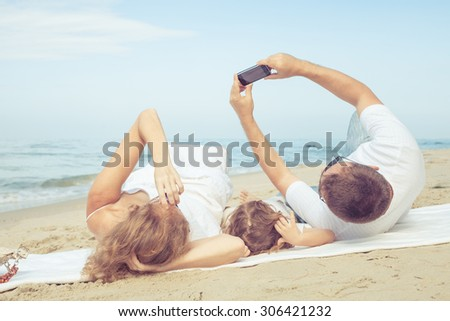 Happy family lying on the beach at the day time. Concept of friendly family. - stock photo