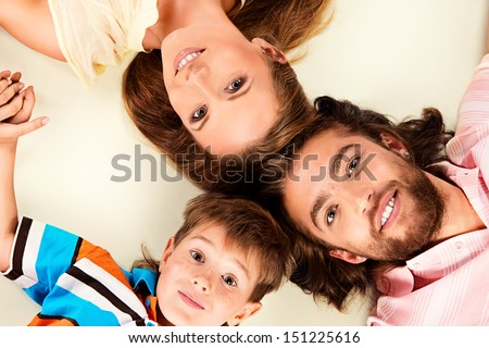 Happy family lying on the floor head to head. Father, mother and son. Isolated over white.