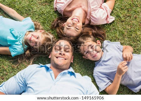 Happy family lying on the grass in a circle smiling at camera in park - stock photo