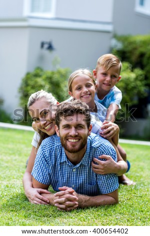 Happy family lying on top of each other in yard - stock photo