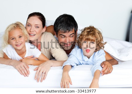 Happy family lying together on bed