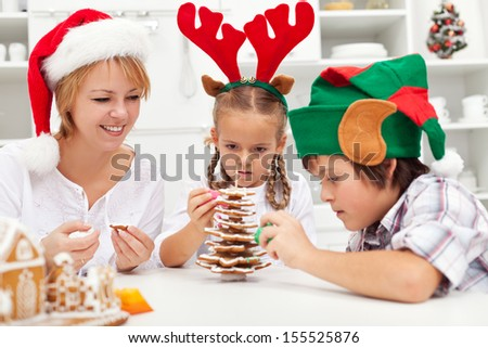 Happy family making a gingerbread cookie christmas tree together - stock photo