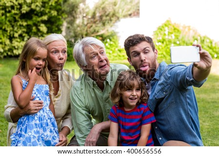 Happy family making face while taking selfie with family while sitting in yard - stock photo
