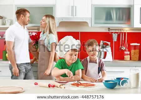 Happy family making pizza in kitchen - stock photo