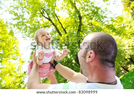 happy family man and baby children playing in bright park while representing happines and parenthood concept