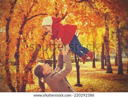 Happy family. Mom and baby daughter for a walk in the autumn - stock photo