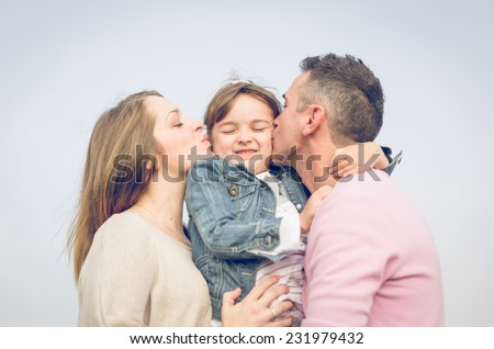 happy family. mom and da holding their daughter and kissing her - stock photo