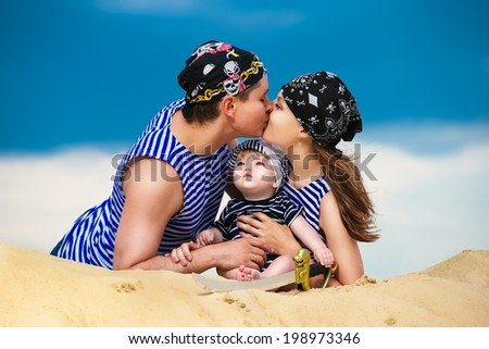 Happy family, mom, dad and little son in striped vests having fun  in the sand outdoors against blue sky background. Summer vacations concept. - stock photo