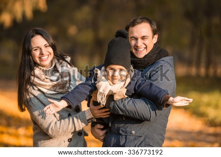 Happy family: Mom Dad and son walking in the park in autumn - stock photo
