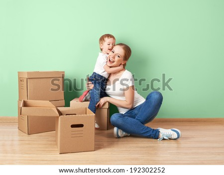happy family mother and baby daughter in an empty apartment near the wall with cardboard boxes relocation - stock photo