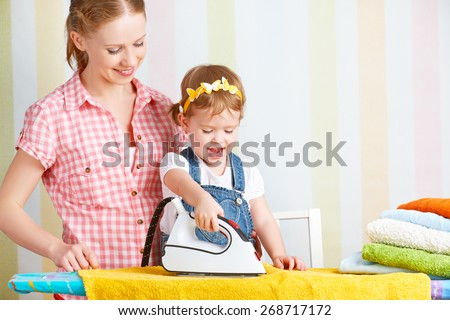 happy family mother and baby daughter together engaged in housework iron clothes iron - stock photo
