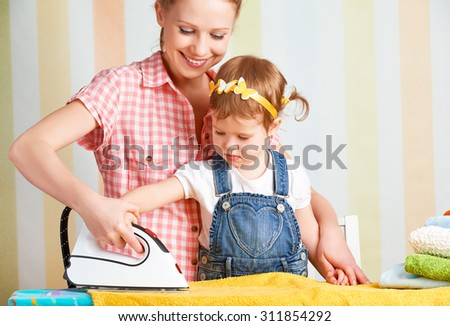 happy family mother and baby daughter together engaged in housework iron clothes iron
