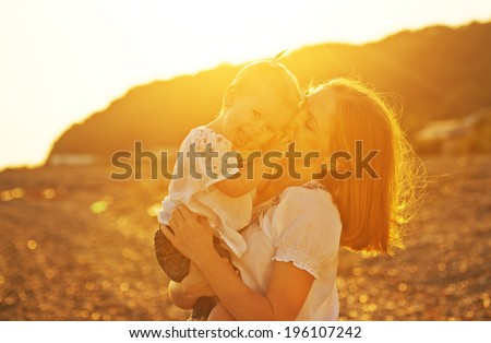 happy family. Mother and baby girl daughter on beach at sunset in nature - stock photo
