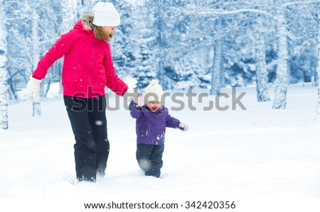 happy family mother and baby girl daughterÃ??run, walk playing  in winter outdoors in the snow - stock photo