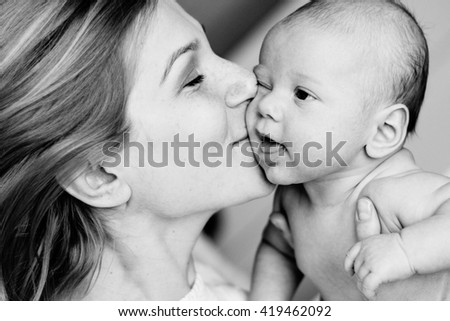 happy family mother and baby having fun playing, kissing laughing on the bed. black and white - stock photo