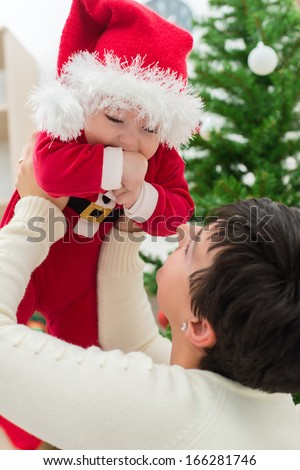 Happy family mother and baby in red Christmas hat - stock photo
