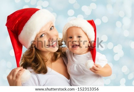 happy family mother and baby in red Christmas hats - stock photo