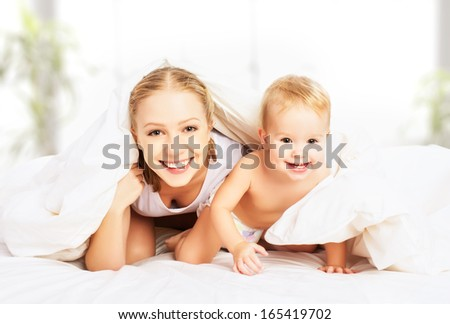 happy family mother and baby peeking out from under the blankets in bed