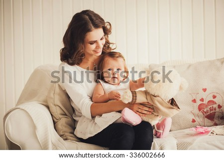happy family. mother and baby sitting on the sofa with a toy - stock photo