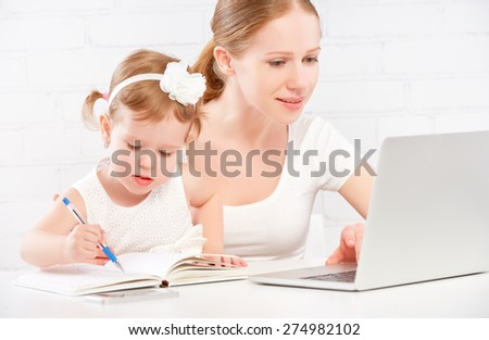 happy family mother and child baby daughter at home working on the computer - stock photo