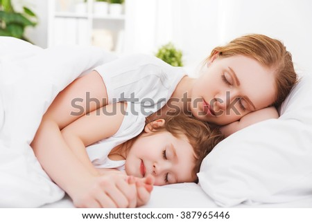happy family mother and child daughter sleeping in bed embracing - stock photo