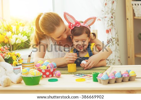 happy family mother and child girl paints eggs for Easter at home - stock photo