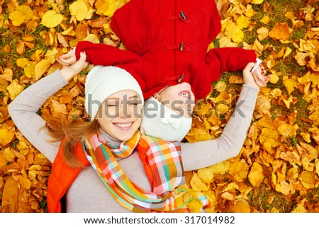 happy family: mother and child little daughter play cuddling on autumn walk in nature outdoors - stock photo