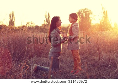 happy family: mother and child little preteen daughter play on autumn walk in nature outdoors. photo toned style instagram filters - stock photo