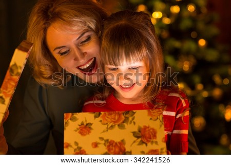 Happy family - mother and daughter child  open together christmas gift box - stock photo