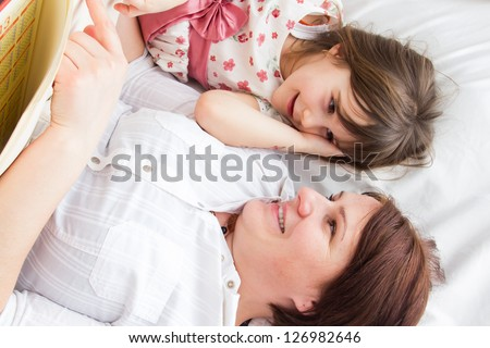 Happy family - mother and daughter in bed reading book and talking, laughing - stock photo