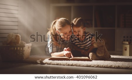 happy family mother and daughter read a book in the evening at home - stock photo