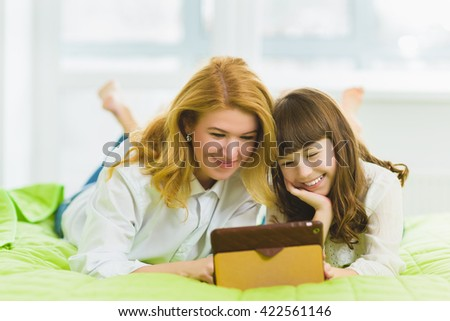 happy family. Mother and daughter sitting on the bed with a tablet - stock photo
