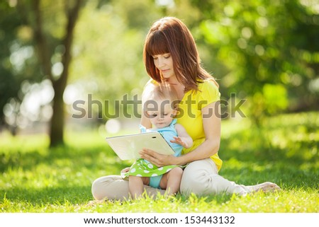 Happy family, mother and daughter with tablet resting in the park.