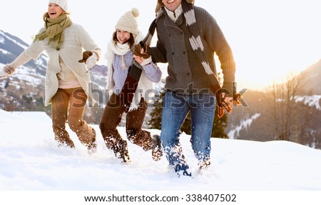 happy family mother and father with girl daughter playing and laughing in winter outdoors - stock photo