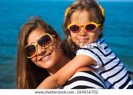 Happy family - mother and girl, are playing and laughing on the beach - stock photo