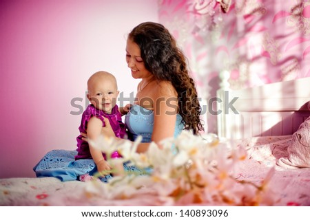 Happy family mother and her child baby girl sitting indoor and smiling