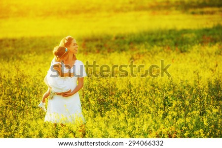 happy family, mother and little daughter girl child in the summer meadow with yellow flowers - stock photo
