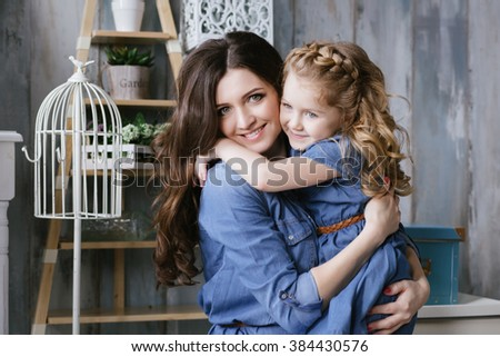 Happy family mother and little daughter hug and laughing dressed in denim dress - stock photo