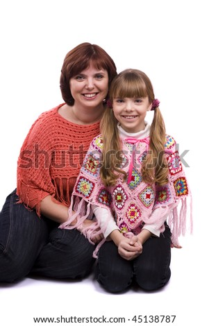 Happy family. Mother and little daughter in winter clothes are smiling . Woman and girl are hugging and posing happily on white background - stock photo