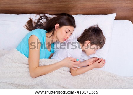 Happy family, mother, and son resting on the white bed. Sleeping family. - stock photo