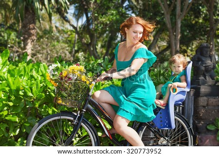 Happy family - mother bicycling and have a fun with little daughter in baby bike seat. Active parents, people outdoors activity and exercises with children on summer vacation in tropical island Bali.   - stock photo