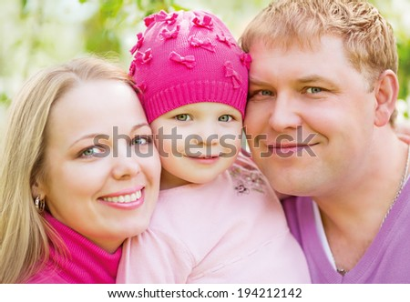 happy family; mother, father and a daughter outdoor in the park - stock photo