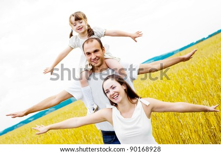 happy family; mother, father and child at the wheat field on a sunny day (focus on the woman) - stock photo
