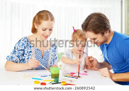 happy family: mother, father  and child baby daughter draw paints - stock photo