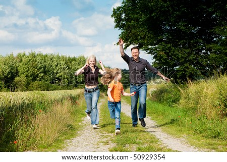 Happy family (mother, father and kid) having a walk in the nature playing tag