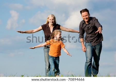 Happy family (mother, father and kid) having a walk in the nature playing tag - stock photo